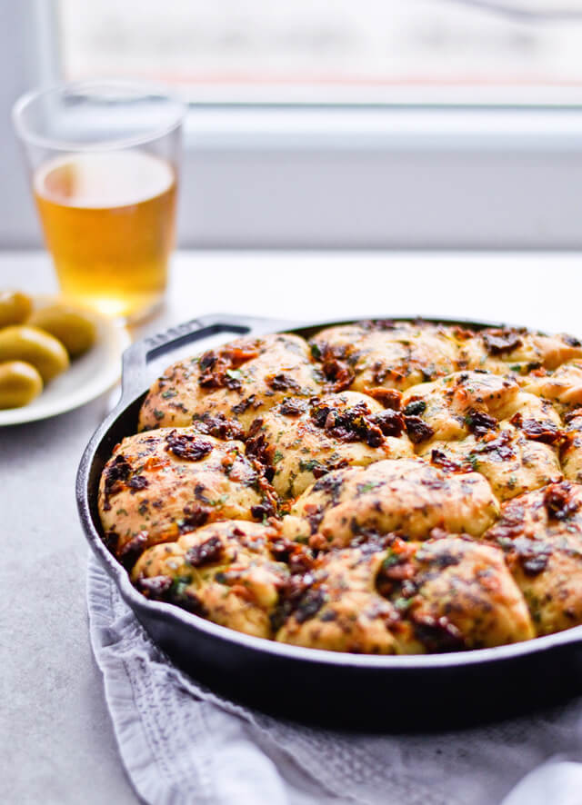 Recipe for sun-dried tomato herb skillet rolls. Dough infused with oregano and rolls drenched with parsley butter and sun-dried tomatoes. Soft, individual rolls straight from the skillet, great for the holiday dinner table. | mitzyathome.com