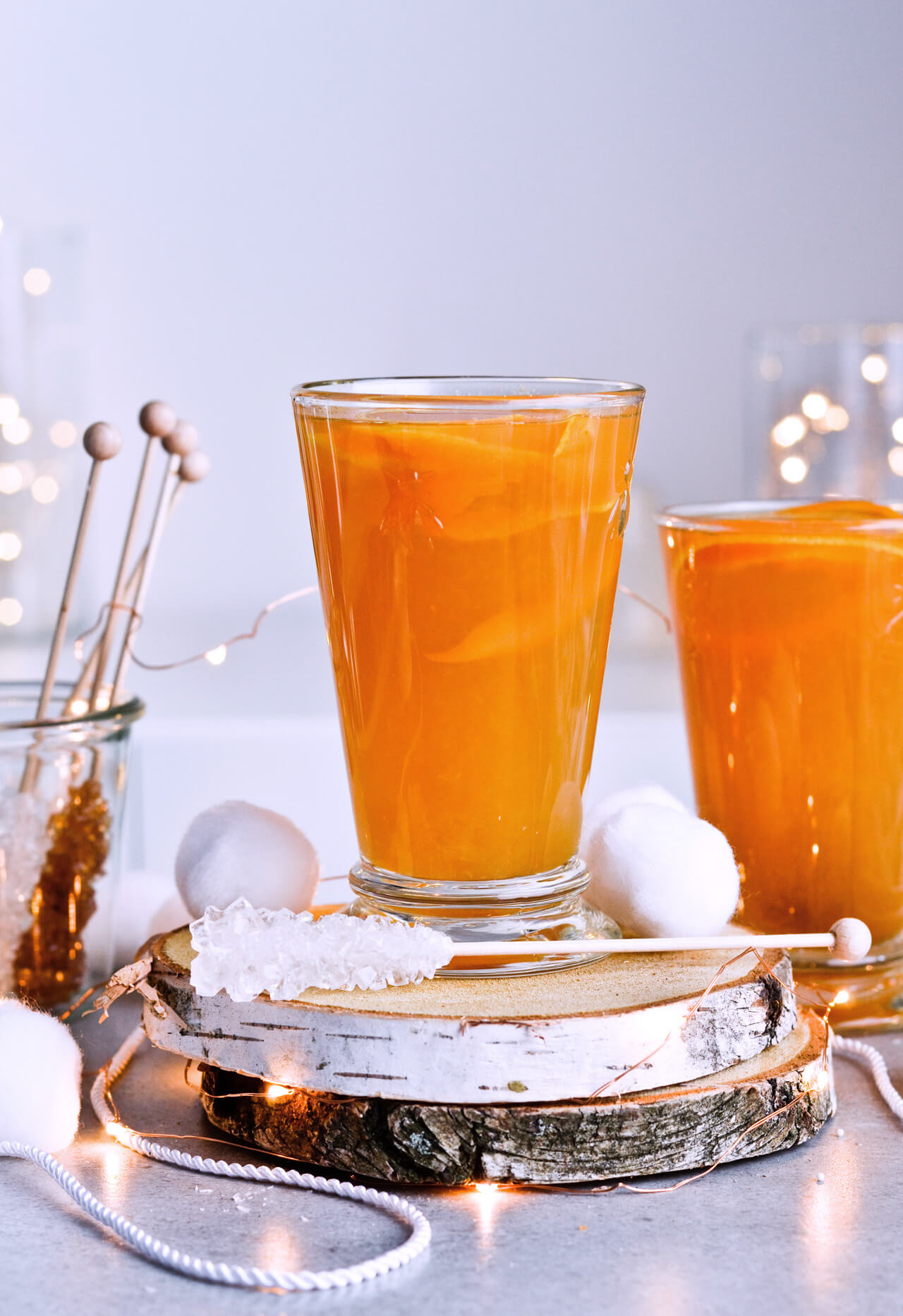 Recipe for Winter tea rum punch, the perfect winter cozy drink! Made with orange juice, honey, ginger beer and cinnamon baked apple teas! Served with orange twists and sugar swizzle sticks. A great cocktail made in 15 minutes! | @mitzyathome mitzyathome.com