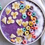 Recipe for creamy, nourishing Coconut blueberry oat smoothie. Made with oats, chia seeds, almond butter and more - this truly is the perfect breakfast! Topped with coconut and pretty froot loops! | mitzyathome.com